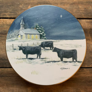Tin with design of 3 black cows in a snowy field with a church in the background