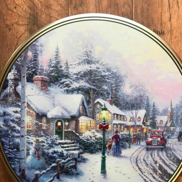 Tin with image of quaint snowy village street