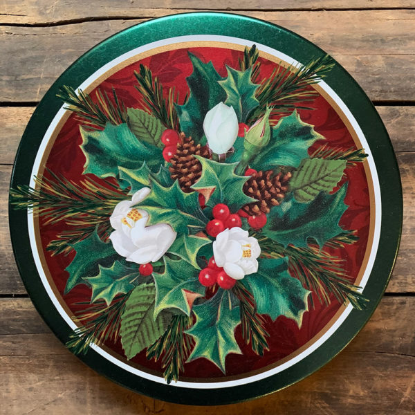 Red and green tin with an image of a Christmas bouquet of holly, fir and pinecones