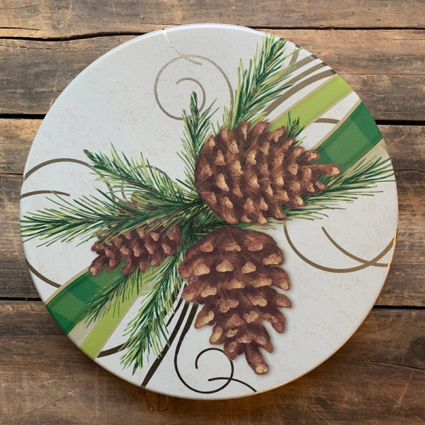 white tin with image of pinecones, branches and green ribbon