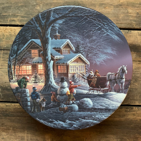 tin with image of snowy winter view with snowman, sleigh and glowing home